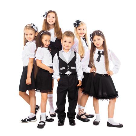 Skupina usmívající se školačky ve školní uniformě, izolovaných na bílém pozadí. Vzdělávání, móda, přátelství koncept. Reklamní fotografie