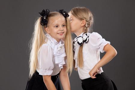 niños en la escuela: Retrato de un par de colegialas habla y comparten secretos. La educación, la moda, el concepto de la amistad. Foto de archivo