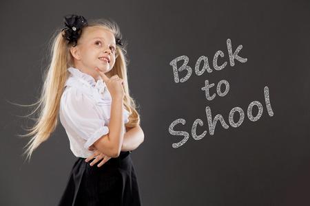 uniformes: Colegiala rubia bastante. Lugar para el texto, fondo de educación. Escuela, concepto de moda