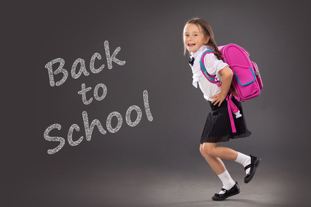uniform student: Little girl with a backpack going to school. Place for text, education background. School, fashion concept Stock Photo