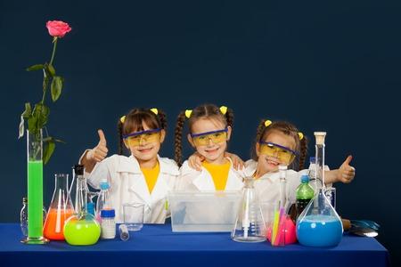 niños estudiando: Felices los niños haciendo experimentos en el laboratorio. La ciencia y la educación. Foto de archivo