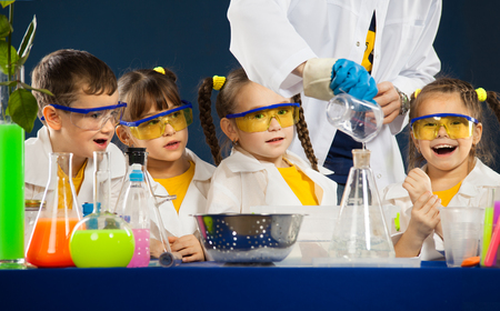 Group happy kids with scientist doing science experiments in the laboratory. Science and education.