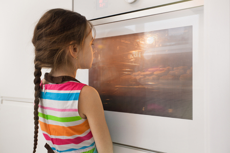 Little girl waiting near the kitchen oven for the homemade cookies. Baking. Children cooking concept