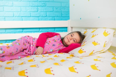 girl lying: Pretty little girl in pajamas lying in bed in the morning