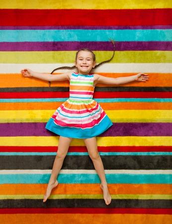 Gelukkig kind liggend op de kleur tapijt achtergrond. Meisje lachend en kijken naar camera Stockfoto