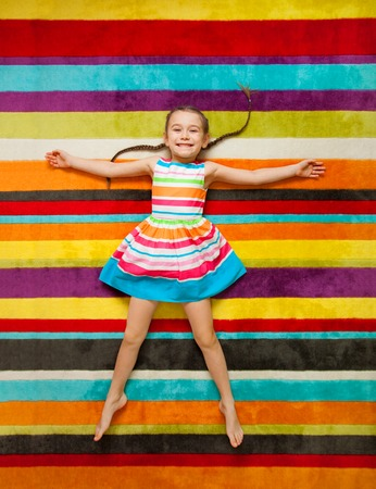 Happy child lying on the color carpet background. Little girl smiling and looking at camera Stock Photo