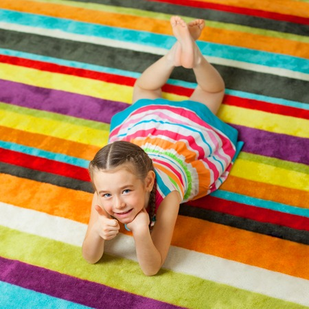 girl lying: Happy child lying on the color carpet background and showing thumbs up. Little girl smiling and looking at camera Stock Photo