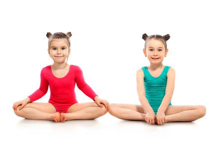 niños sentados: Little girls gymnast on a white background. Active lifestyle concept