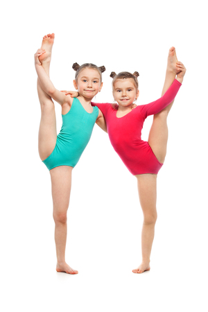 Flexible little girls gymnasts, isolated on white background. Sport, active lifestyle concept