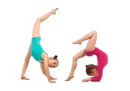 acrobacia: los niños flexibles gimnastas haciendo hazaña acrobática, aisladas sobre fondo blanco. Deporte, estilo de vida activo concepto Foto de archivo
