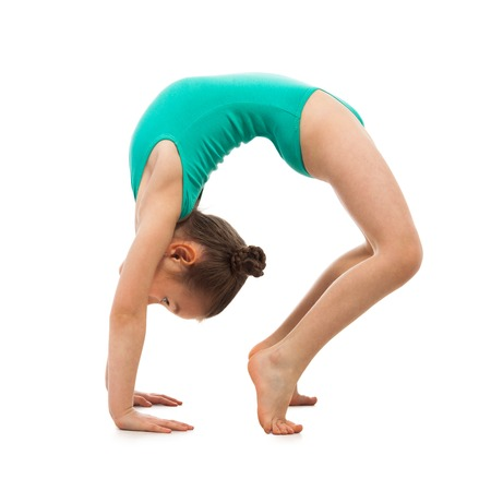 Flexible little girl gymnast doing a bridge on a white background. Sport, active lifestyle concept