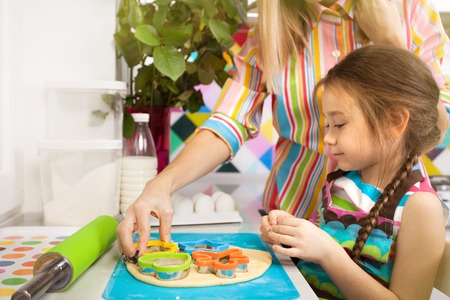 kiss biscuits: Little girl preparing a cookie on kitchen for her mother. Family, children cooking and help concept Stock Photo