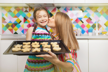help: Little girl preparing a cookie on kitchen for her mother. Family, children cooking and help concept Stock Photo