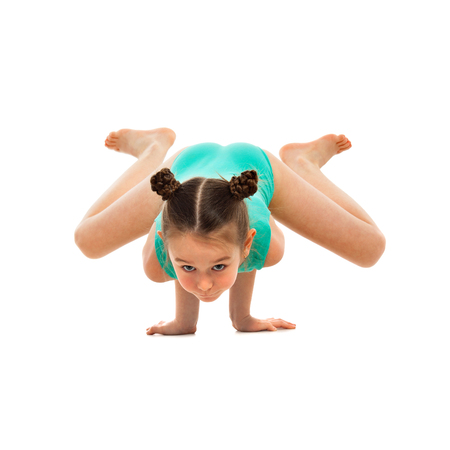 feat: Flexible little girl gymnast doing acrobatic feat, isolated on white background. Sport, active lifestyle concept Stock Photo