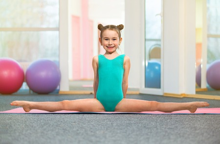 Little girl gymnast sitting in the cross split in gym. Sport, active lifestyle concept