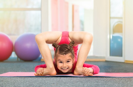 feat: Flexible little girl gymnast doing acrobatic exercise in gym. Sport, training, active lifestyle concept