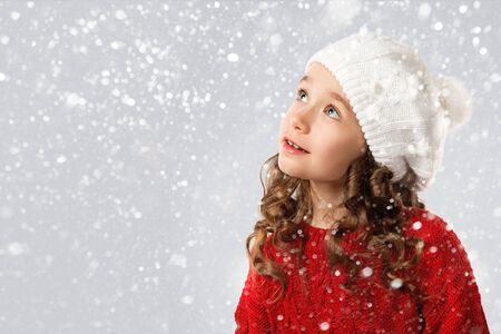 Merry Christmas and Happy New Year Holidays! Cute little girl in winter clothes on snow background. Space for Your Text.