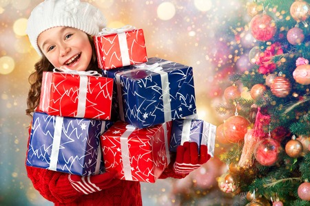 Merry Christmas and Happy New Year Holidays! Happy little girl with many gifts near Christmas tree. Christmas sale Фото со стока