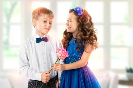ragazza innamorata: Graziosi bambini, ragazzo dà una bambina di fiori. San Valentino. amore del bambino