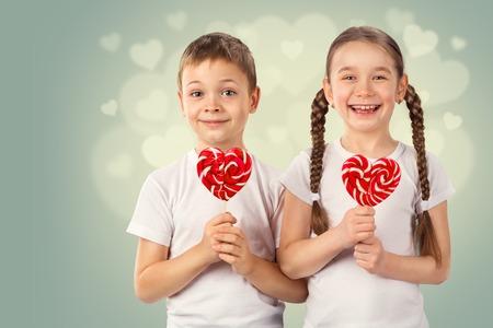 Malý chlapec a dívka s cukroví červeným lízátkem ve tvaru srdce. Valentýnský den portrét umění. Reklamní fotografie - 71735862