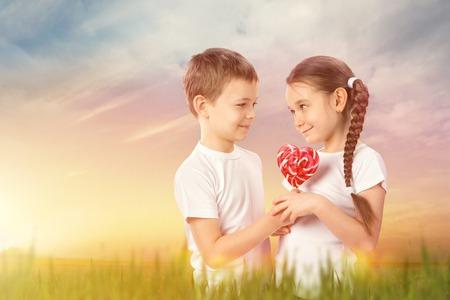 Boy gives a little girl candy red lollipop in heart shape on sunset field. Valentines day Reklamní fotografie - 71569623