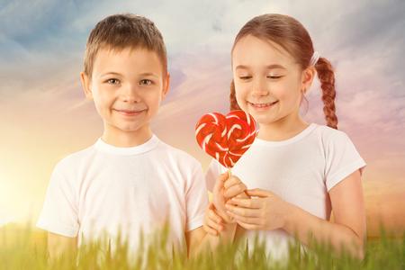 Chlapec dává malou dívku candy červené lízátko ve tvaru srdce na západ slunce pole. Valentýn. Děti milují. Reklamní fotografie - 71623114
