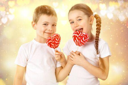 Malý chlapec a dívka s cukroví červeným lízátkem ve tvaru srdce. Valentýnský den portrét umění. Reklamní fotografie - 71567734