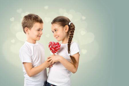 Chlapec dává malou dívku candy červené lízátko ve tvaru srdce. Valentýn Reklamní fotografie - 71735861