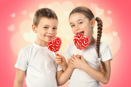 Little boy and girl with candy red lollipop in heart shape on pink background. Valentines day art portrait. Reklamní fotografie - 71569620
