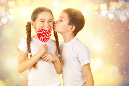 first love: Boy kisses little girl with candy red lollipop in heart shape. Valentines day art portrait