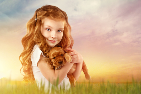 Beautiful red-haired little girl with red puppy in field at sunset. Fashion, style kid and pet friendship