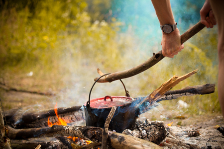 outdoor fireplace: Camping kitchenware - pot on the fire at an outdoor campsite.