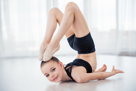 Flexible child, beautiful little gymnast girl doing gymnastic exercises or exercising in fitness class Stock Photo