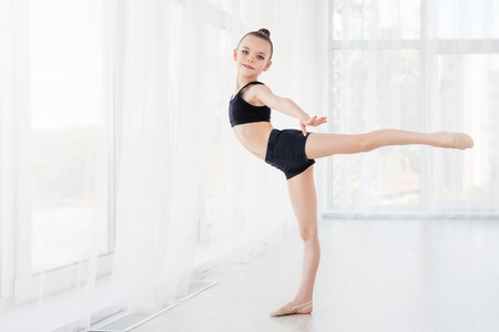 Flexible child, beautiful little gymnast girl doing gymnastic exercises or exercising in fitness class Banco de Imagens
