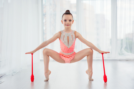 Beautiful little gymnast girl in pink sportswear dress, performing art gymnastics element with mace in fitness class