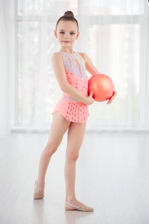 Schöne kleine Gymnastik Mädchen in rosa Sportbekleidung Kleid, Durchführung Kunst Gymnastik-Element mit Ball in Fitness-Klasse Standard-Bild - 81213034