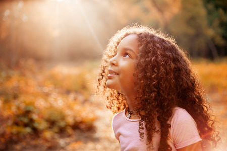 Afro américaine mignonne petite fille aux cheveux bouclés reçoit les rayons du soleil miracle du ciel Banque d'images
