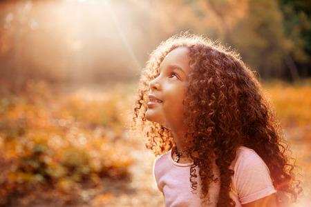 Afro Amerikaanse schattig klein meisje met krullend haar ontvangt wondere zonnestralen uit de hemel Stockfoto