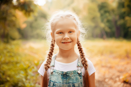 Adorable smiling little blonde girl with braided hair. Cute child having fun on a sunny summer day outdoor.