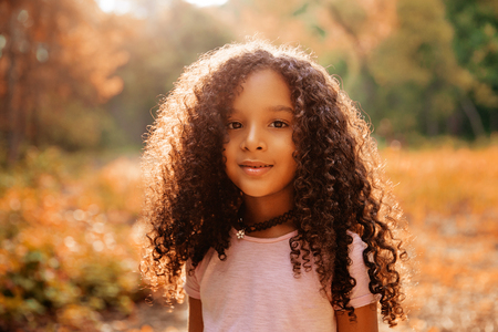 Outdoor portrait of a cute afro american happiness little girl with curly hairl. Stock Photo