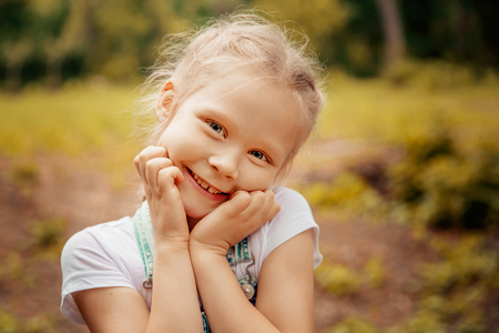 Adorable smiling little blonde girl with braided hair. Cute child having fun on a sunny summer day outdoor. Sun light. Glow sun. Happy day. Warm photo. Outdoor portrait.