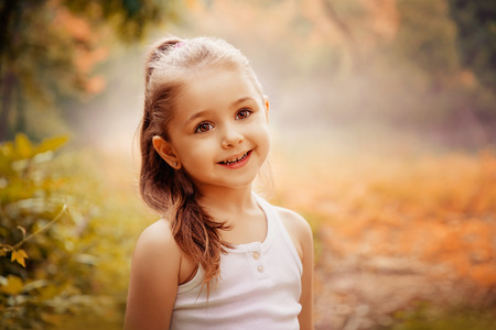 Outdoor portrait of a cute smiling little girl. Children Smiling Happiness Concept