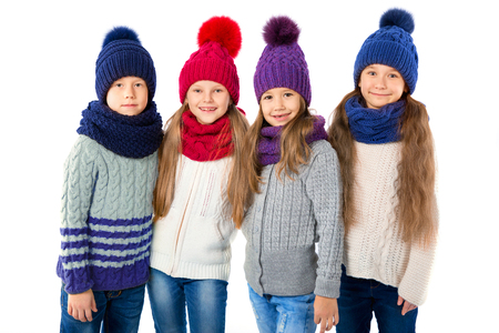 Group of cute kids in winter warm hats and scarfs isolated on white. Children winter clothes Stock Photo