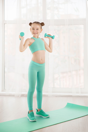 Little sporty girl gymnast in sportswear doing exercises on a mat indoor