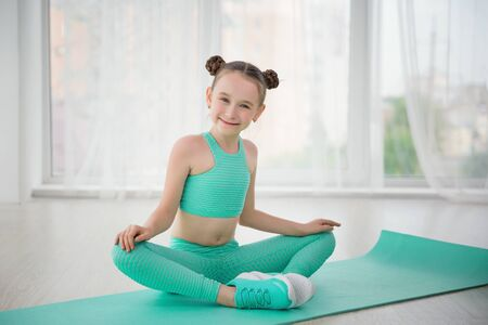 Little sporty girl gymnast in sportswear doing exercises on a mat indoor Foto de archivo