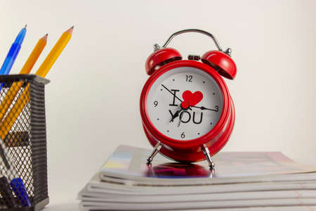 A red alarm clock stands on a stack of school exercise books. Back white background.