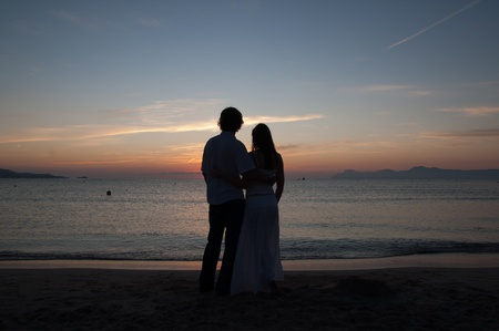 Silhouette of young couple at seaside at sunrise photo