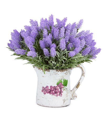 Jug with wild flowers isolated on white photo