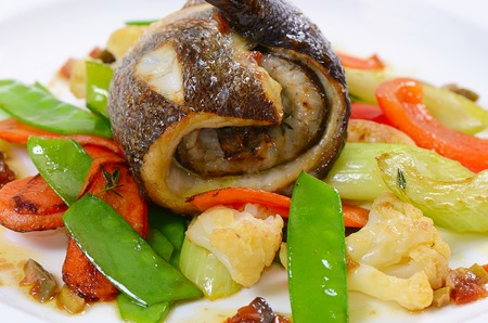 Sea bass fillet with spring vegetables and olive sauce photo