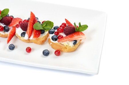 Profiteroles with berries currant  strawberries and blueberries photo